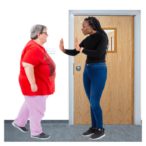 A person is being stopped from leaving their home by a member of staff.